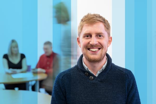 Smart-casual smiling man in meeting room with two people identifying talent